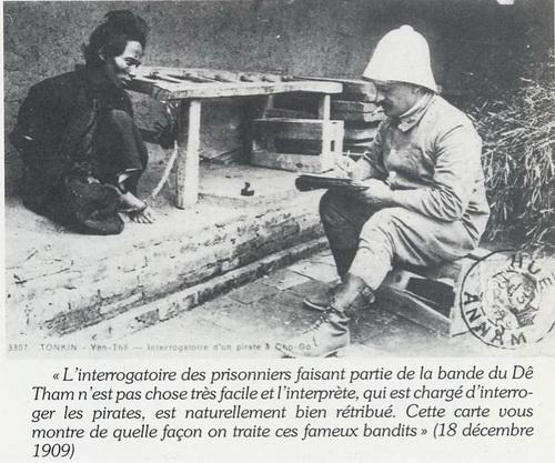 Một nghĩa sĩ đang bị thẩm vấn (dịch: Thẩm vấn những tù nhân thuộc băng cướp của Đề Thám không phải là chuyện dễ và người  thẩm vấn bọn cướp này đương nhiên được tưởng thưởng hậu hĩ. Tấm thiệp này cho quý vị biết cách đối xử với bọn cướp nổi tiếng này(18 tháng 12 năm 1909). (Hình ảnh lấy trong cuốn Le Việt-Nam Autrefois của Michel Germain, năm 1989)
