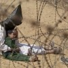 31/3/2003, Iraq. Jean-Marc Bouju, France, The Associated Press. An Iraqi man comforts his four-year-old son at a holding center for prisoners of war, in the base camp of the US Army 101st Airborne Division near An Najaf. The boy had become terrified when, according to orders, his father was hooded and handcuffed. A soldier later severed the plastic handcuffs so that the man could comfort his child. Hoods were placed over detainees' heads because they were quicker to apply than blindfolds. The military said the bags were used to disorient prisoners and protect their identities. It is not known what happened to the man or the boy.
