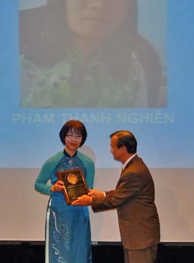 Tiến Sĩ Nguyễn Bá Tùng (phải) trao giải cho bà Kim Oanh, đại diện cô Phạm Thanh Nghiên. (Hình: MLNQVN cung cấp)