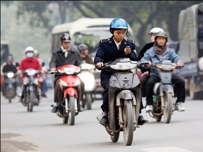Hình (NPR): Một người vừa chạy xe gắn máy vừa dùng điện thoại di động tại Hà Nội.
