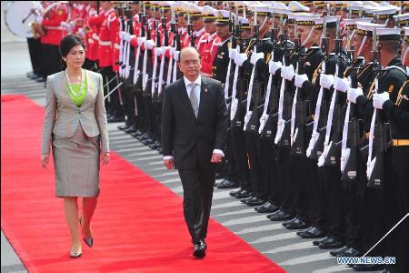 Hình (Xinhua): Tổng Thống Miến Điện Thein Sein (phải) và Thủ Tướng Thái Lan Yingluck Shinawatra duyệt hàng quân danh dự tại phi trường Bangkok, 23-7-2012 nhân dịp ông viếng thăm xã giao Thái Lan.