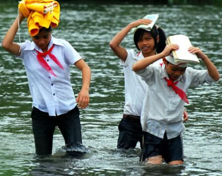 Đội áo lạnh, sách vở trên đầu, dò dẫm vượt sông.