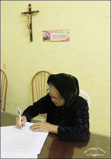 Cụ Trần Thị Mạp, mẹ ông Đoàn Văn Vươn, đang viết đơn kêu cứu cho các con. Ảnh: nuvuongcongly