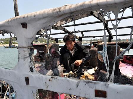 Thuyền trưởng Phạm Quang Thạnh bên chiếc tàu bị Trung Quốc bắn cháy. Ảnh: NLĐ