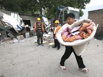 Một người dân buộc phải dọn dẹp đồ đạc khi nhà cửa bị phá (REUTERS)