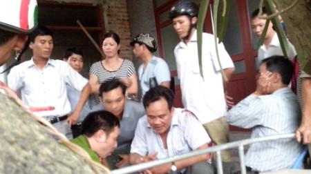 Anh Kỷ (ôm vết thương, bìa phải) và anh Ngọc tường trình vụ việc với cơ quan công an - Ảnh: Ái Châu