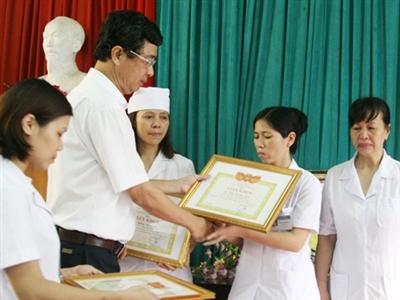 Phó Giám đốc Sở Y tế Hà Nội trao tặng giấy khen kèm 350.000 đồng tiền thưởng cho 3 cá nhân dũng cảm tố cáo tiêu cực tại Bệnh viện Đa khoa Hoài Đức, Hà Nội. Ảnh: Thái Hà.