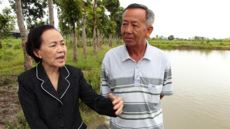 Bà Trần Ngọc Sương kiểm tra tình hình nuôi cá tại ao nuôi của công ty - Ảnh: Chí Quốc