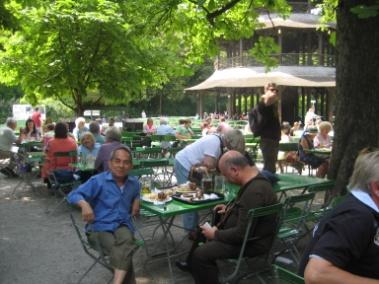 Món Schweinshaxe ăn với bánh mì Brezel trong vườn cây mát mẻ