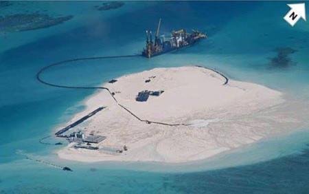 … vào ngày 25 tháng Hai 2014, bức ảnh này được chụp. Nó cho thấy Trung Quốc đã xây một hòn đảo nhân tạo trên rạn san hô. Bên cạnh nhà giàn cũ (ở phía dưới bên trái) đã có thêm nhiều kết cấu vào thời điểm này, trong số đó rõ ràng là một đường băng. Hai tuần sau đó…. Hình: AFP/ DFA