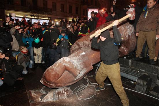 Người biểu tình kéo đổ, rồi dùng búa đập nát tượng Lenine trên Quảng trường Maidan. Ảnh: NBCNews.com