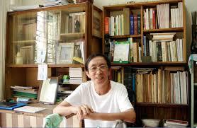 Dương Nghiễm Mậu gẫy chân, ngồi cười trước tủ sách, hai tay tựa trên khung đi / walker [photo by Ngô Thế Vinh 09/ 2006] 2012_ Từ Hải Ngoại Truyện.