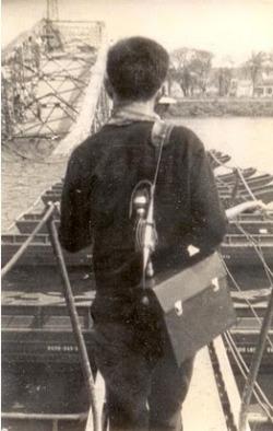 Phóng viên chiến tranh Dương Nghiễm Mậu đi qua nhịp cầu Tràng Tìền bị giựt sập trong Tết Mậu Thân, Huế 1968 [photo by Đinh Cường]
