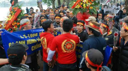 """Nhóm người mặc áo đỏ in chữ """"DLV"""" giăng cờ đỏ búa liềm trước tượng đài, ngăn cản người dân đặt hoa, thắp hương tưởng niệm các liệt sĩ Gạc Ma. Ảnh đăng trên VnExpress"""