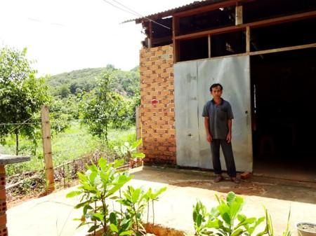 Nông dân Lê Văn Thương buồn rầu đứng trước căn nhà tuềnh toàng, dột nát của mình Ảnh: Dương Cầm