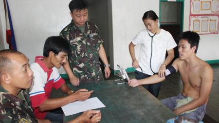 Anh Dũng (thứ hai từ trái) làm phiên dịch trong buổi khám sức khỏe cho ngư dân - Ảnh: Đình dân