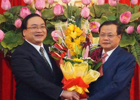 Nguyên Bí thư Hà Nội Phạm Quang Nghị (phải) tặng hoa chúc mừng tân Bí thư Hoàng Trung Hải. Ảnh: Q.P/ Vnexpress