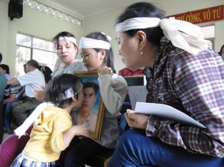 Con gái nạn nhân Ngô Thanh Kiều hôn di ảnh cha trong phiên xử 5 công an. Ảnh NLĐ