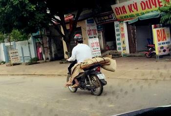 Do không có tiền thuê xe ô tô nên gia đình chị P đã nhờ người quen sử dụng xe máy chở thi thể về mai táng. Ảnh & chú thích: Dân Việt