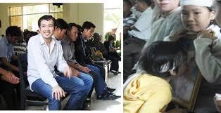 Cảnh ở phiên sơ thẩm, bị cáo cười tươi và các con của nạn nhân bên di ảnh cha