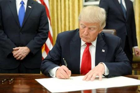 Tân Tổng thống Donald Trump ký ban hành các văn bản đầu tiên sau khi tuyên thệ nhậm chức hôm 20/01/2017. Ảnh AFP